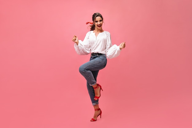 Radosna kobieta w dżinsach, biała bluzka tańczy na różowym tle. nowoczesna dziewczyna z czerwoną szminką iw stylowych obcasach raduje się na na białym tle.