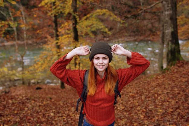 Radosna kobieta w kapeluszu sweterku z plecakiem na plecach gestykuluje rękami w parku