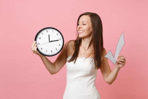 Radosna kobieta w koronkowej białej sukni trzymająca znacznik wyboru i okrągły budzik