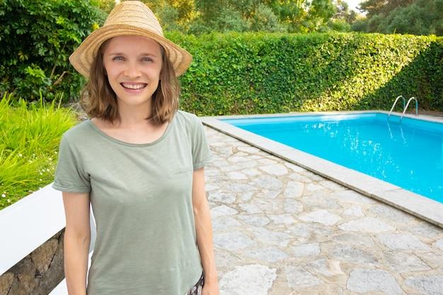 Radosna kobieta w lato stroju pozyci w ogródzie