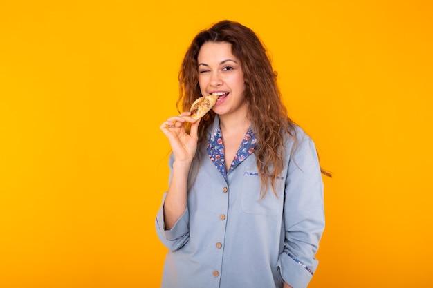 Radosna kobieta w modnej piżamie zamierza zjeść małego pysznego rogalika na żółtym tle