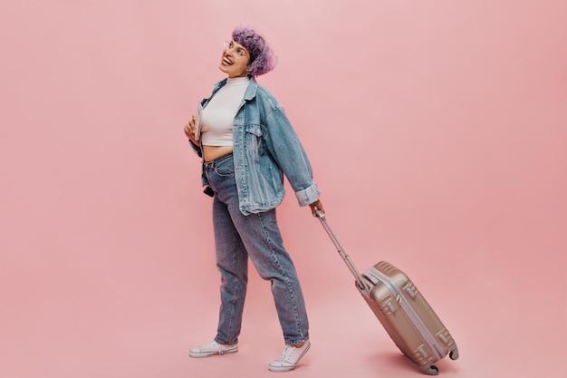 Radosna kobieta w okularach i lekkiej koszulce i obcisłych dżinsach kroczy i trzyma walizkę. wesoła kobieta ze stawianiem fioletowe włosy.