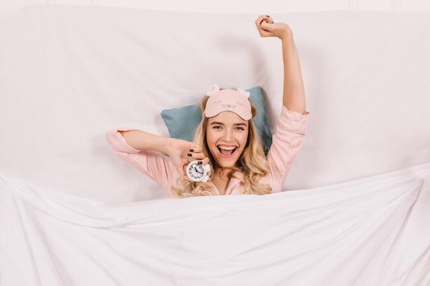Radosna kobieta w piżamie rozciągająca się w łóżku