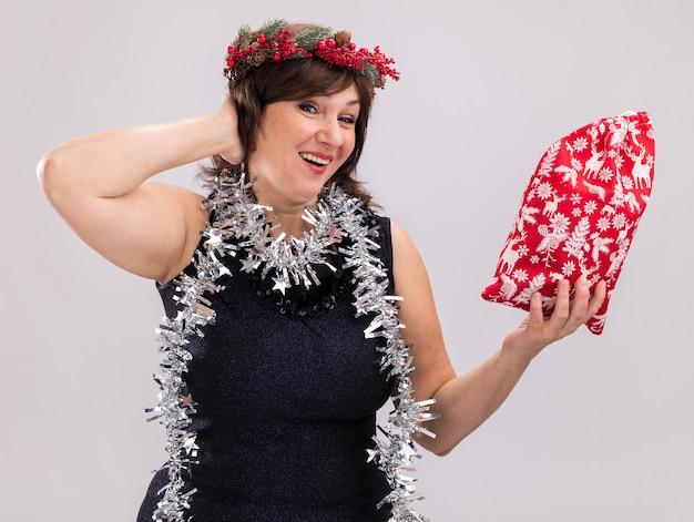 Radosna kobieta w średnim wieku ubrana w świąteczny wieniec na głowę i świecącą girlandę na szyi trzymająca worek z prezentami bożonarodzeniowymi trzymająca rękę za głową na białej ścianie