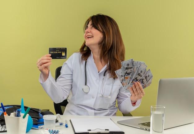 Radosna kobieta w średnim wieku ubrana w szlafrok medyczny i stetoskop siedząca przy biurku z narzędziami medycznymi i laptopem trzymająca pieniądze i kartę kredytową patrząc na bok na białym tle