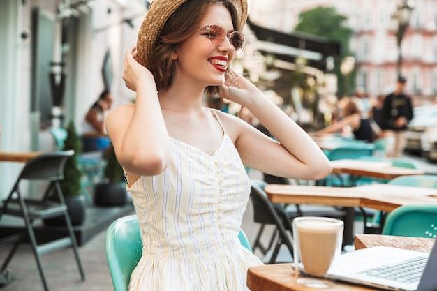 Radosna kobieta w sukience i słomkowym kapeluszu po odpoczynku