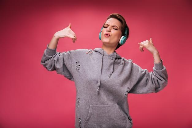 Radosna kobieta w szarej bluzie z kapturem słuchająca swojej ulubionej piosenki w słuchawkach. krótkowłosa dama w bluzie tańczy i lubi muzykę na różowym tle