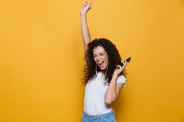Radosna kobieta w wieku 20 lat z kręconymi włosami śpiewa, trzymając smartfon i słuchając muzyki przez słuchawki izolowane na żółto