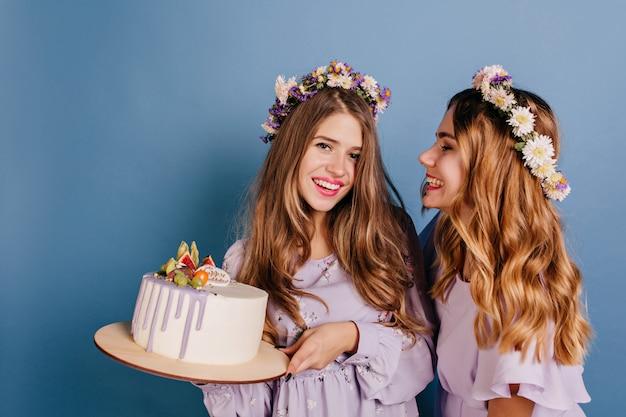 Radosna kobieta w wieńcu kwiatów patrząc na tort, który trzyma jej siostrę