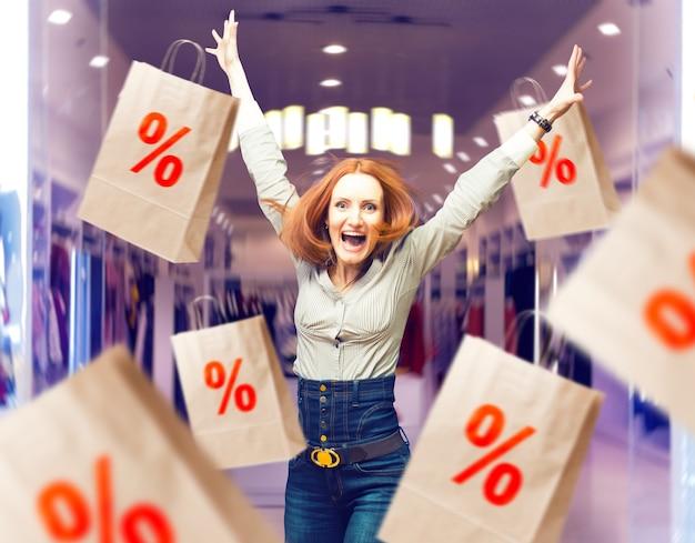 Radosna kobieta wśród sprzedaży papierowych toreb w sklepie