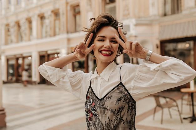 Radosna kobieta z czerwonymi ustami pokazującymi znaki pokoju w mieście. nowoczesna kobieta z krótkimi włosami w białej bluzce z czarną koronką uśmiechnięta na ulicy.
