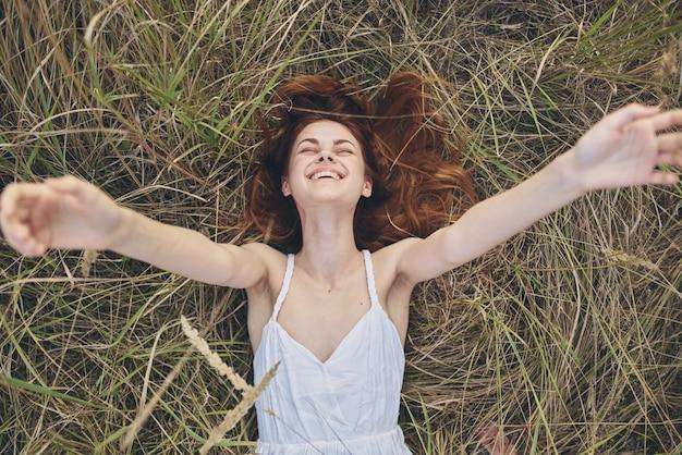 Radosna kobieta z podniesionymi rękami leży na słomie wolności odpoczynku
