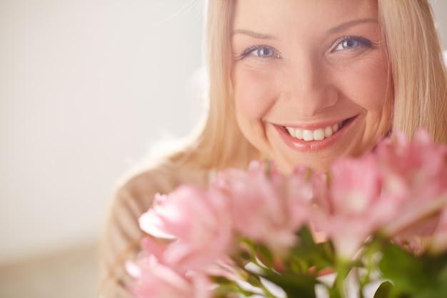 Radosna kobieta z różowymi kwiatami