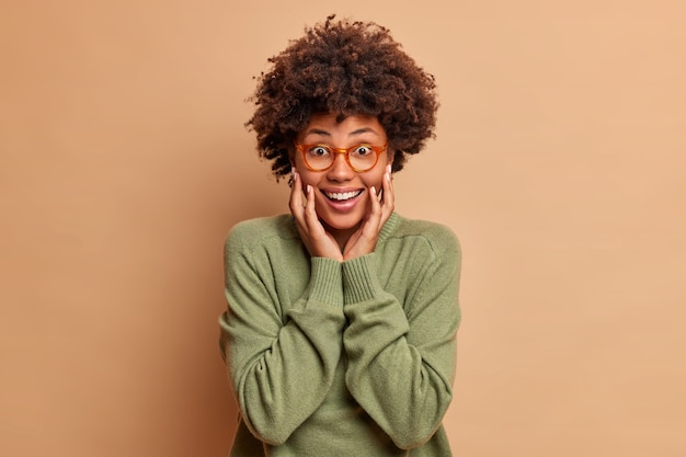 Radosna kobieta z włosami afro trzyma ręce na policzkach uśmiecha się radośnie patrzy z przodu nosi okulary optyczne i sweter odizolowany na brązowej ścianie