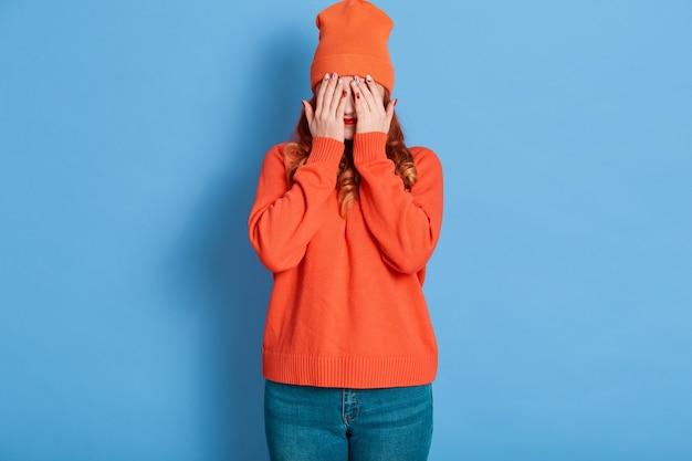 Radosna kobieta zakrywa oczy dłońmi, próbuje się przed kimś ukryć