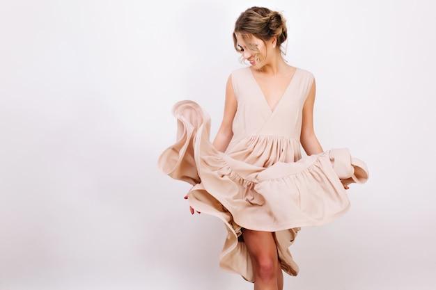 Radosna kręcona dziewczyna z uroczą fryzurą pozuje figlarnie podczas przymierzania nowej stylowej sukienki. szczupła młoda kobieta w modny strój vintage taniec, na białym tle.