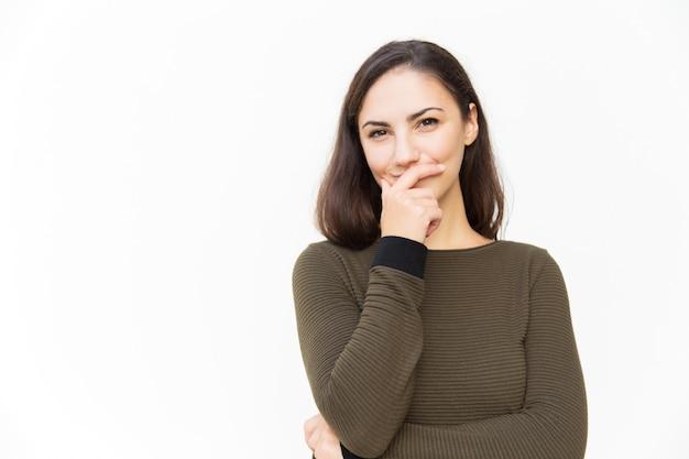 Radosna łacińska kobieta zakrywa usta ręką