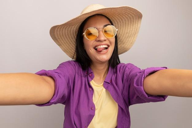 Radosna ładna brunetka kaukaska dziewczyna w okularach przeciwsłonecznych z kapeluszem plażowym wystawia język i udaje, że trzyma aparat, robiąc selfie na białym tle
