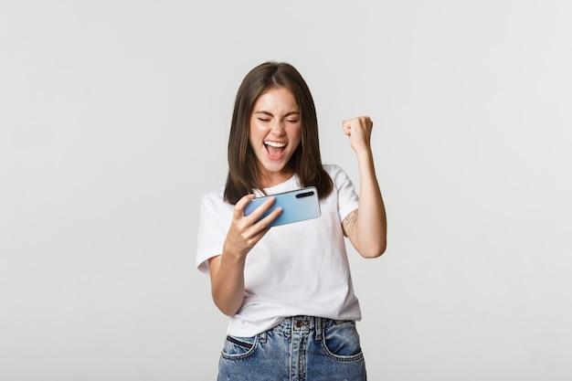 Radosna ładna dziewczyna grająca w grę na telefon komórkowy i pompka pięścią, zadowolona z wygranej na białym tle