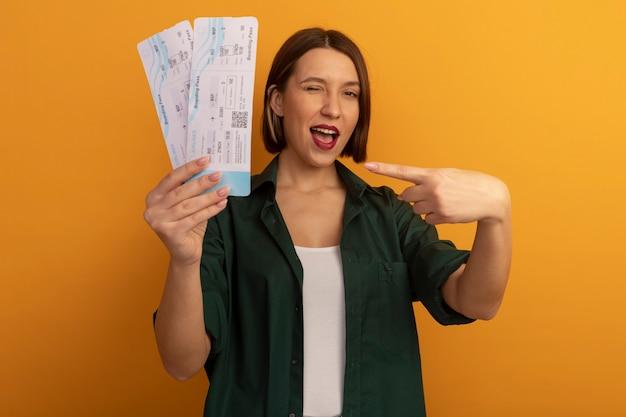 Radosna ładna kaukaska kobieta mruga oczami, trzymając i wskazując na bilety lotnicze na pomarańczowo