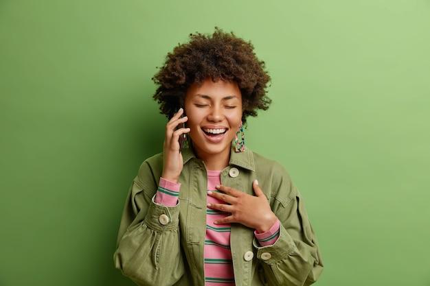 Radosna ładna kobieta chichocze pozytywnie rozmawiając przez smartfona, dzwoni do najlepszej przyjaciółki ubranej w modną kurtkę odizolowaną od zielonej ściany