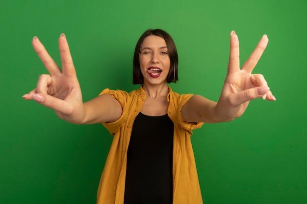 Radosna ładna kobieta mruga okiem wystawiającym język i gestami ręki znak zwycięstwa dwiema rękami odizolowanymi na zielonej ścianie