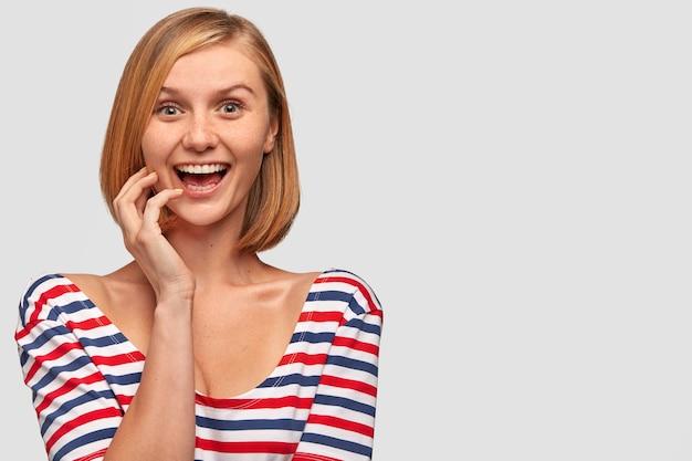 Radosna ładna kobieta o europejskim wyglądzie, pozytywnie się uśmiecha, ma zdumiony wyraz twarzy