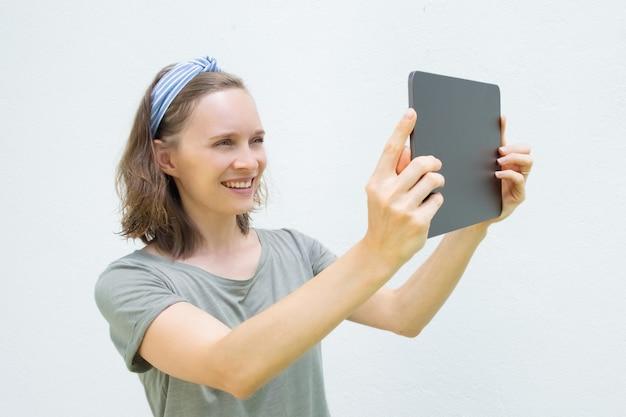 Radosna ładna kobieta używa pastylkę do robienia zdjęć