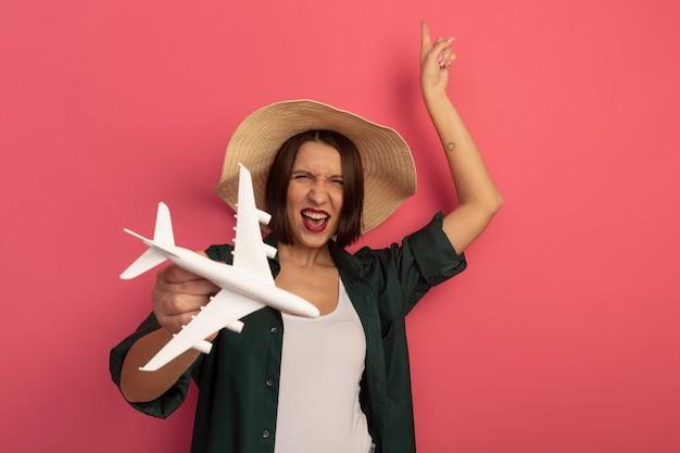 Radosna ładna kobieta w kapeluszu plażowym trzyma model samolotu i wskazuje na białym tle na różowej ścianie