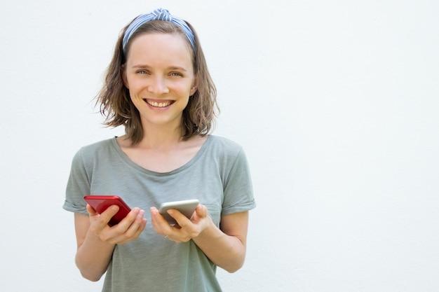 Radosna ładna kobieta w letnie ubrania przy użyciu dwóch telefonów