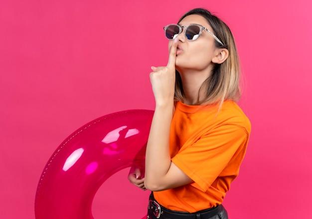 Radosna ładna młoda kobieta w pomarańczowej koszulce w okularach przeciwsłonecznych pokazująca gest shh z palcem wskazującym, trzymając różowy nadmuchiwany pierścień na różowej ścianie