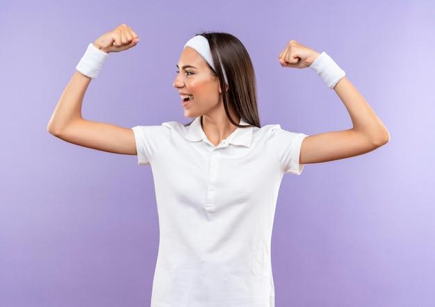 Radosna, ładna sportowa dziewczyna nosząca opaskę i nadgarstek, gestykulując mocno, patrząc na bok odizolowany na fioletowej ścianie