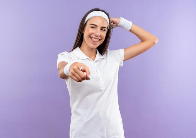 Radosna ładna sportowa dziewczyna nosząca opaskę i opaskę gestykulującą silnym mruganiem wskazującym i pokazującym język na fioletowej ścianie
