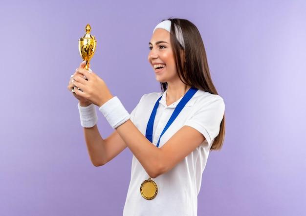 Radosna, ładna sportowa dziewczyna nosząca opaskę na głowę, opaskę i medal, trzymająca i patrząca na filiżankę odizolowaną na fioletowej ścianie