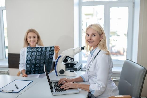 Radosna lekarka pracująca przy laptopie i koleżanka ze skanem mrt siedząca zajęta obok stołu