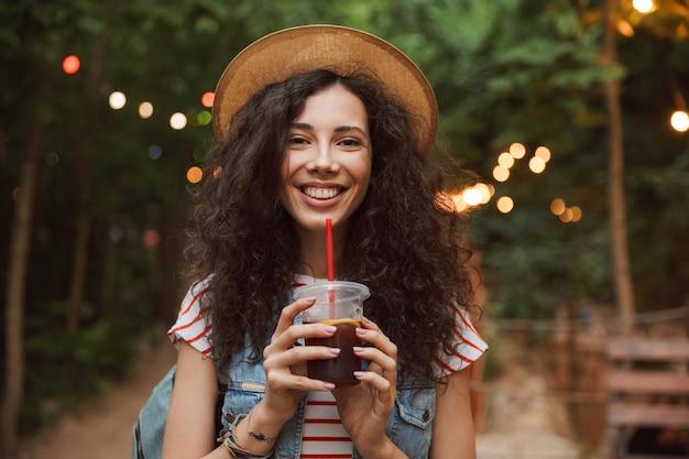 Radosna letnia kobieta w słomkowym kapeluszu, patrząc na ciebie popijając napój z plastikowego kubka i spacerując po zielonym parku z kolorowymi lampami