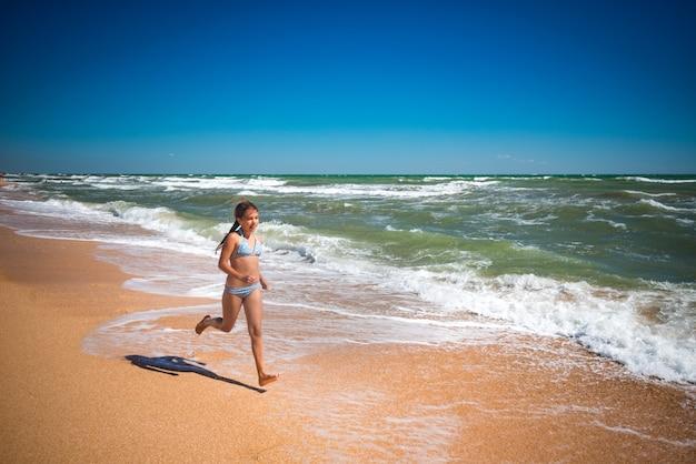 Radosna mała aktywna dziewczyna skacząca na falach wzburzonego morza w słoneczny, ciepły letni dzień. koncepcja rodzinne wakacje z dziećmi.