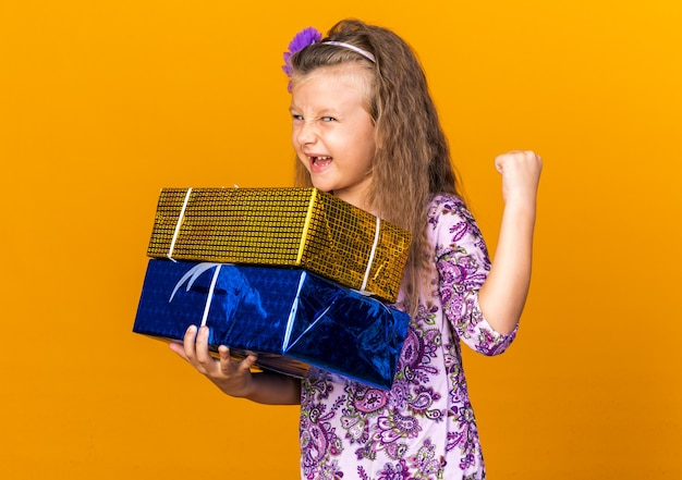 Radosna mała blondynka trzyma pudełka z prezentami i trzyma pięść na białym tle na pomarańczowej ścianie z miejsca na kopię