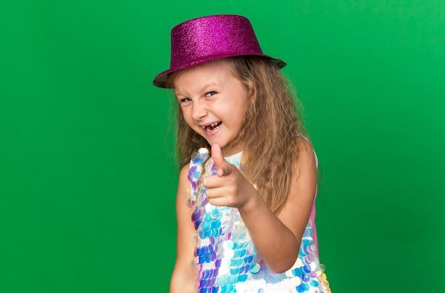 Radosna mała blondynka z fioletowym kapeluszem imprezowym wskazującym na zielonej ścianie z miejscem na kopię