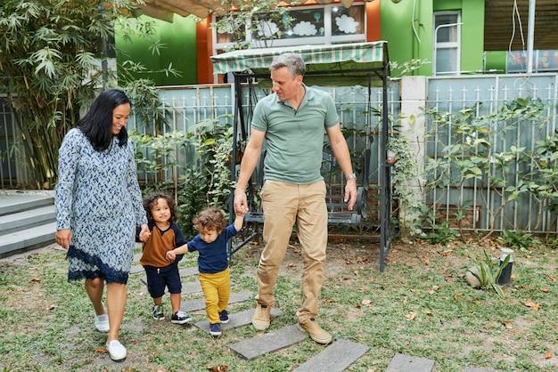 Radosna mama, ojciec i dwaj mali synowie spędzają razem czas na domowym podwórku