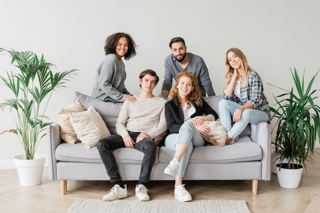 Radosna, międzykulturowa nastolatka w swobodnym stroju wypoczywa na kanapie podczas wspólnego spędzania czasu w domu
