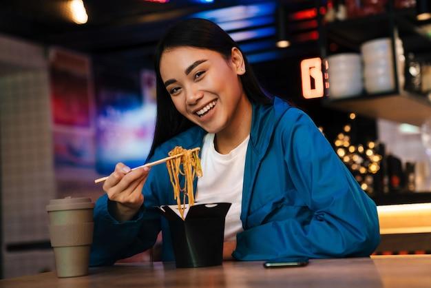 Radosna miła azjatycka kobieta je chińskie makarony i uśmiecha się siedząc w kawiarni