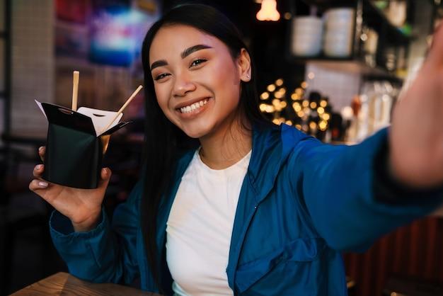 Radosna miła azjatycka kobieta trzymająca chiński makaron i uśmiechająca się podczas robienia selfie w kawiarni
