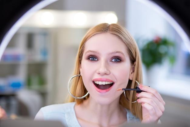 Radosna miła kobieta będąca w świetnym nastroju patrząc na swoją twarz w lustrze