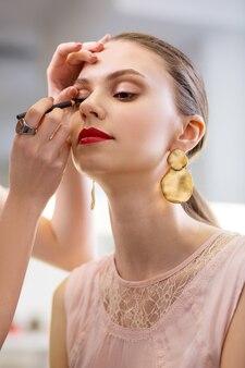 Radosna miła kobieta, która ma makijaż u wizażysty, a jednocześnie chce wyglądać pięknie