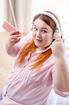 Radosna miła kobieta nosząca słuchawki podczas słuchania muzyki