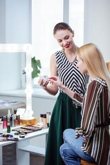 Radosna miła kobieta patrząca na swojego klienta, polecając jej kosmetyki kosmetyczne