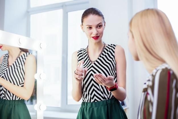Radosna miła kobieta rozmawiająca ze swoim klientem przygotowująca się do makijażu