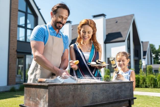 Radosna miła rodzina przygotowująca grilla, ciesząc się razem