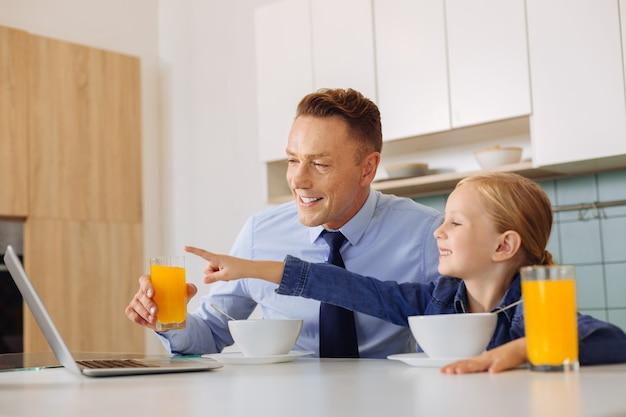 Radosna miła śliczna dziewczyna siedzi przy kuchennym stole i wskazując ręką na ekranie laptopa
